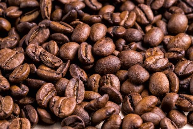 Ярко-коричневый жареный кофе в зернах фона. Premium Фотографии