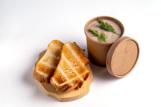 テイクアウトまたは青色の背景に食品の配達のための紙の使い捨てカップのエンドウ豆のスープ Premium写真