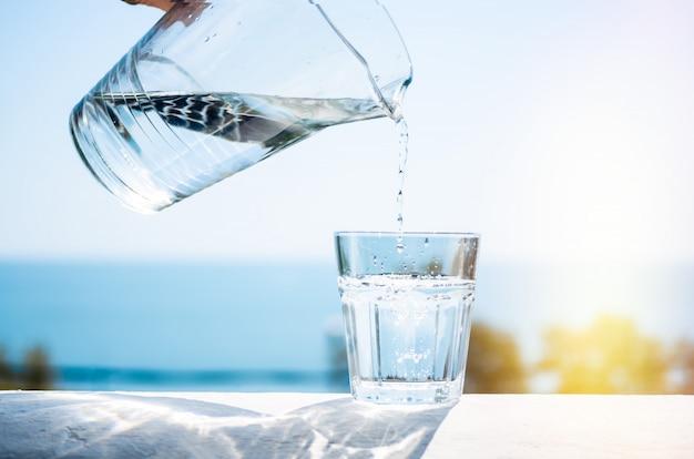 Очищенная вода наливается из стеклянного кувшина в стакан. Premium Фотографии