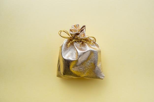 Подарочная сумка из золотой ткани на желтом фоне. Premium Фотографии