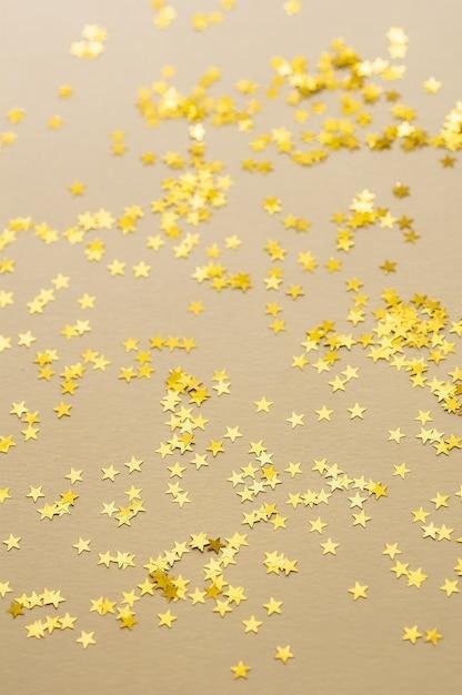 明るい背景に紙吹雪のお祝いの黄金の星が点在しています。 Premium写真