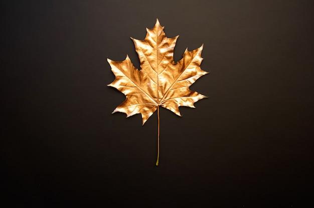 Золотой кленовый лист на черном фоне Premium Фотографии