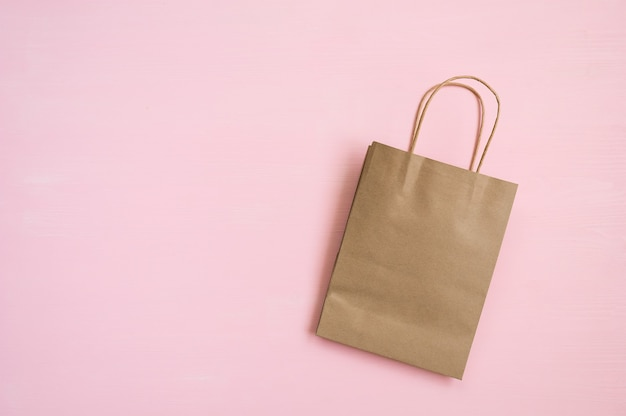 ピンクの背景に買い物のためのハンドルを持つ空の茶色の紙袋 Premium写真