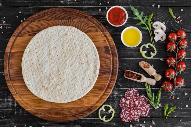 ピザの製造に生地と野菜の準備。木製の背景上のピザの生産のための原料 Premium写真