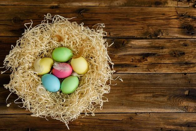 イースターケーキと木製のテーブルの上のカラフルな卵。 Premium写真