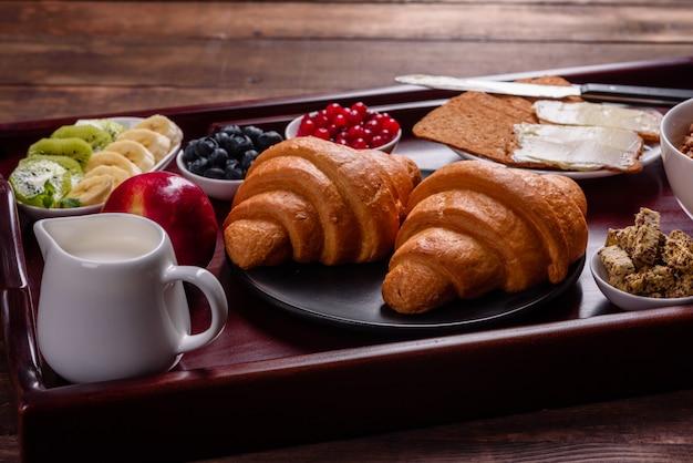 焼きたてのクロワッサンと美しい木製のテーブルに熟した果実のおいしい朝食 Premium写真