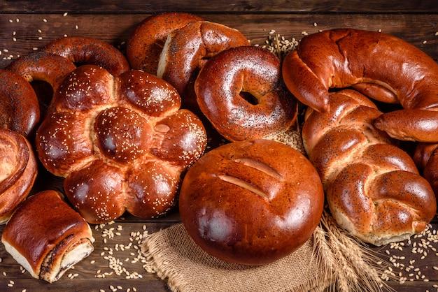 Композиция из свежих запеченные сладкие булочки с маком и вареньем. сладкая выпечка выложена в виде композиции на деревянный стол Premium Фотографии
