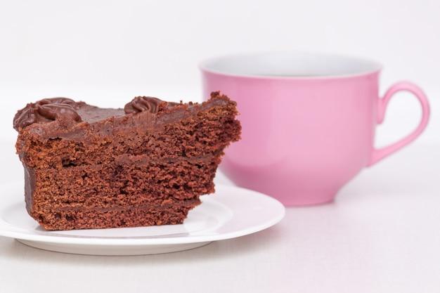 明るい背景上のテーブルの上にピンクのコーヒーカップと皿の上のおいしいチョコレートケーキ Premium写真