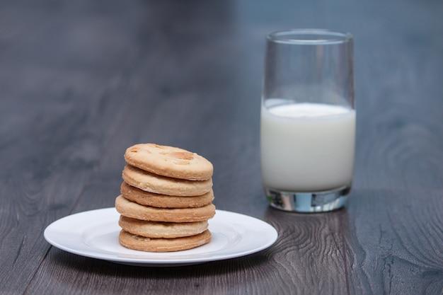 ガラスと木製の背景に白い皿にアーモンドとおいしいクッキービスケット Premium写真