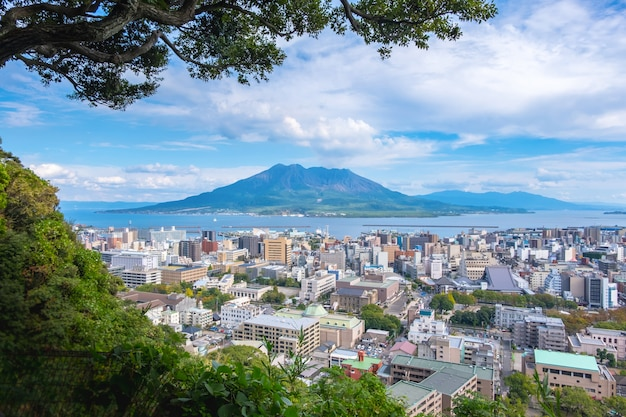 桜島の山、海、青い空を背景に街並み Premium写真