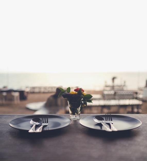 Романтический ужин с прекрасным видом на пляж, тарелки, ложки и вилки на столе Premium Фотографии
