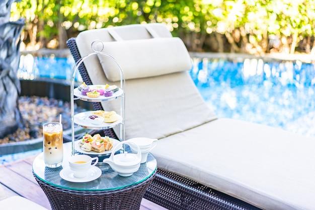 スイミングプールの周りのテーブル近くの椅子にラテコーヒーと熱いお茶とアフタヌーンティーセット 無料写真
