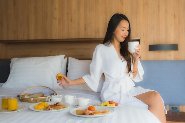 肖像画の美しい若いアジア女性は幸せな寝室のベッドで朝食をお楽しみください 無料写真
