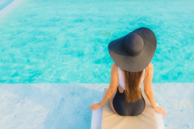 Улыбка красивой молодой азиатской женщины портрета счастливая ослабляет вокруг открытого бассейна в курорте гостиницы Бесплатные Фотографии