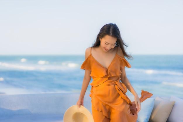海オーシャンビーチの周りの肖像画美しい若いアジア女性の幸せな笑顔 無料写真
