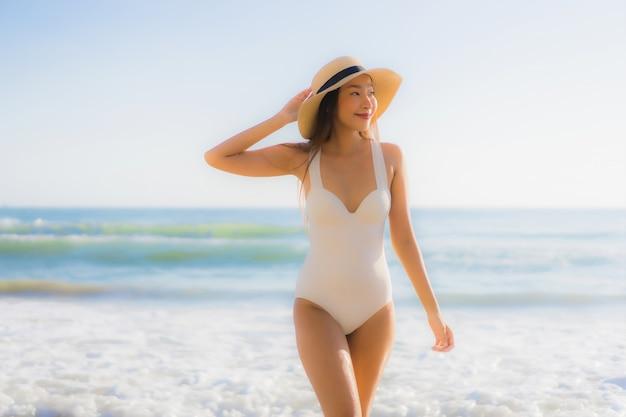 Улыбка красивой молодой азиатской женщины портрета счастливая вокруг пляжа океана моря Бесплатные Фотографии
