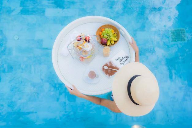 Женщина портрета красивая молодая азиатская наслаждается с послеполуденным чаем или завтрак плавая на бассейн Бесплатные Фотографии