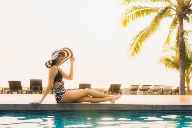 肖像画美しい若いアジアの女性は、夕日や日の出のヤシの木とホテルリゾートの屋外スイミングプールの周りでリラックスします。 無料写真