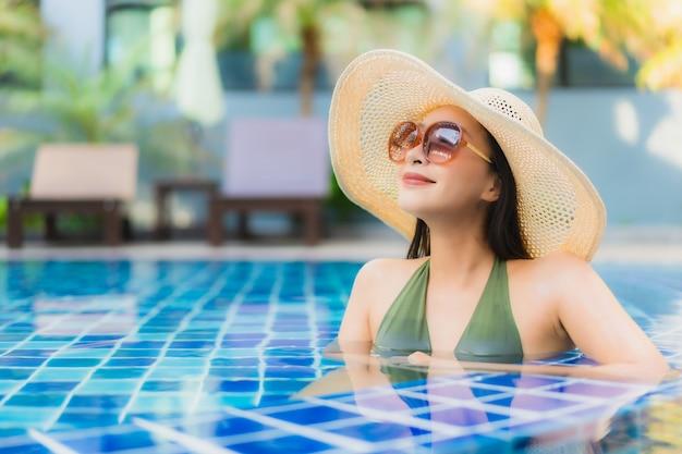 肖像画の美しい若いアジア女性はホテルリゾートのスイミングプールの周りでリラックスします。 無料写真