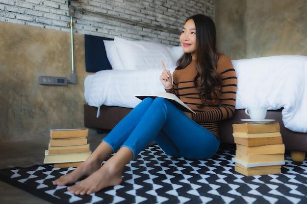 Молодая азиатская женщина с кофейной чашкой и прочитанной книгой Бесплатные Фотографии
