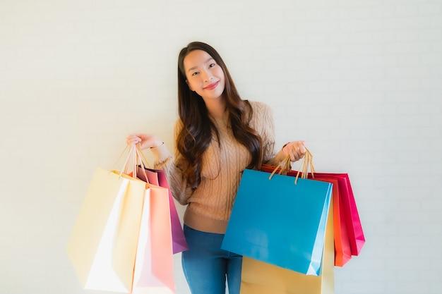 Улыбка красивых молодых азиатских женщин портрета счастливая с хозяйственной сумкой Бесплатные Фотографии