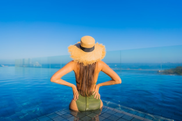美しい若いアジア女性の幸せな笑顔は、休暇中の旅行のためのホテルリゾートの屋外スイミングプールの周りでリラックスします。 無料写真