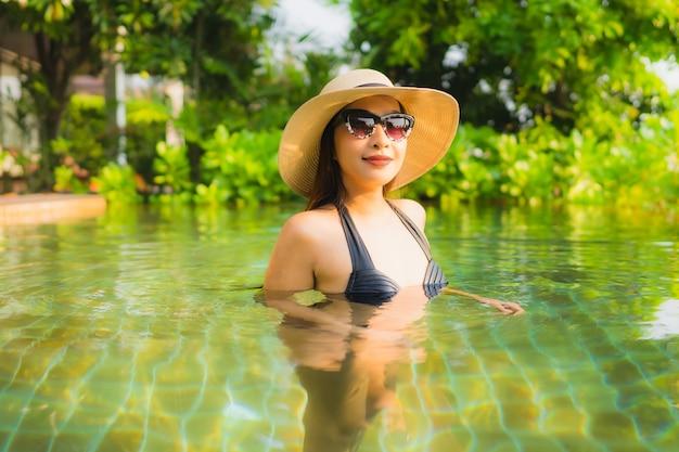 肖像画の美しい若いアジア女性はレジャー休暇のホテルリゾートのスイミングプールでリラックスします。 無料写真
