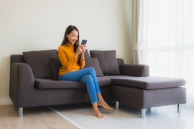 リビングルームの枕が付いているソファーでスマートな携帯電話を使用して肖像若いアジア女性 無料写真