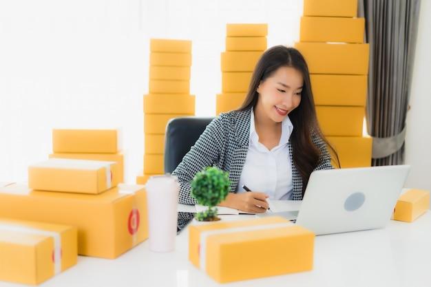 肖像画の美しい若いアジアビジネス女性自宅でラップトップ携帯電話で段ボール箱を出荷の準備ができていると仕事 無料写真