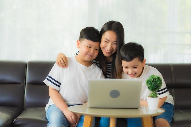 ラップトップを使用して彼女の息子を持つ美しい若いアジア女性ママ 無料写真