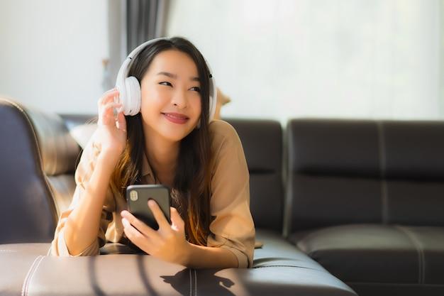 Молодая азиатская женщина использует смартфон на диване с наушниками Бесплатные Фотографии