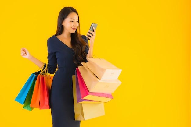 ショッピングバッグと美しい若いアジア女性の肖像画 無料写真
