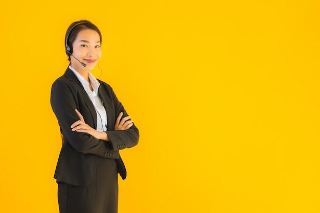 Женщина красивого молодого дела портрета азиатская с наушниками или шлемофоном Бесплатные Фотографии