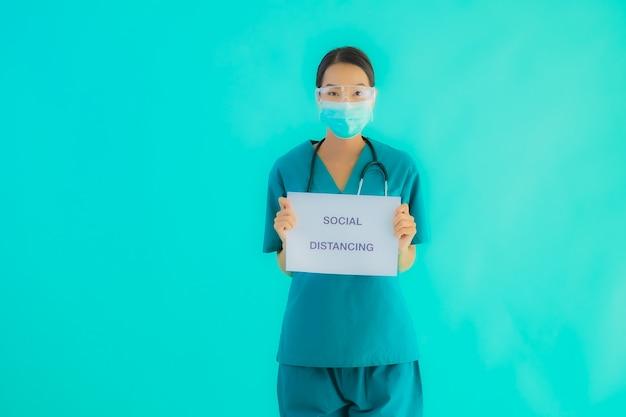 若いアジアの医師の女性着用マスクショーペーパーボード上の社会的距離 無料写真