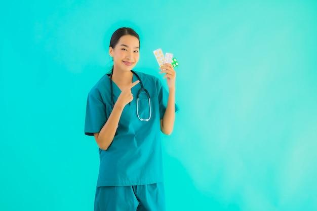 Женщина доктора портрета красивая молодая азиатская с пилюлькой или лекарством и медициной Бесплатные Фотографии