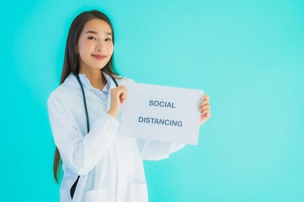 肖像画の社会的な距離と記号の紙の美しい若いアジア医師女性 無料写真
