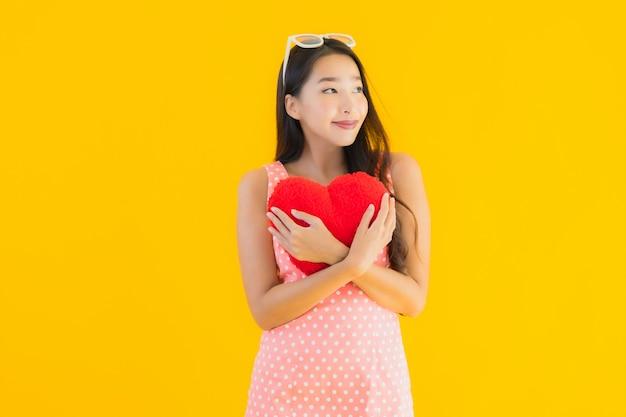 Женщина портрета красивая молодая азиатская с подушкой сердца Бесплатные Фотографии