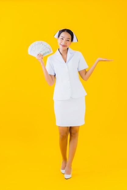 肖像画の多くの現金とお金を持つ美しい若いアジア女性タイの看護師 無料写真