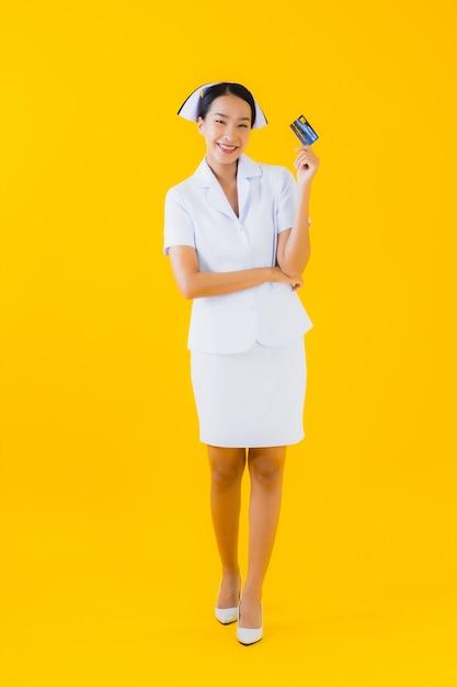 クレジットカードでの美しい若いアジア女性タイの看護師の肖像画 無料写真