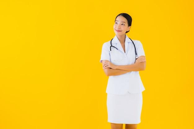 肖像画の美しい若いアジアの女性タイの看護師は患者の仕事の準備ができて幸せな笑顔を笑顔します。 無料写真