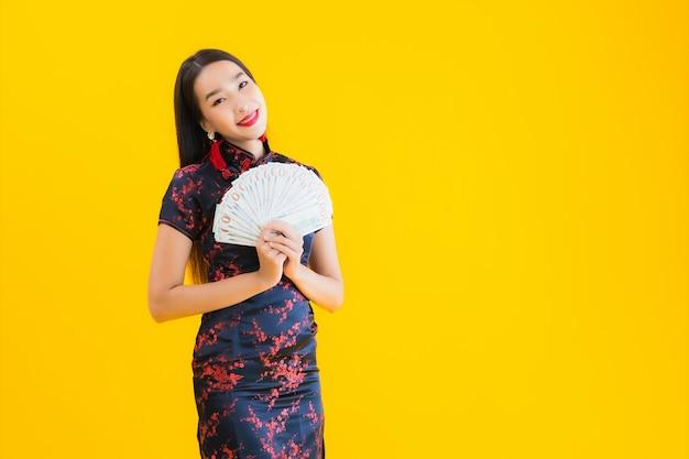 美しい若いアジアの女性の肖像画はチャイナドレスを着て、たくさんの現金を保持しています。 無料写真