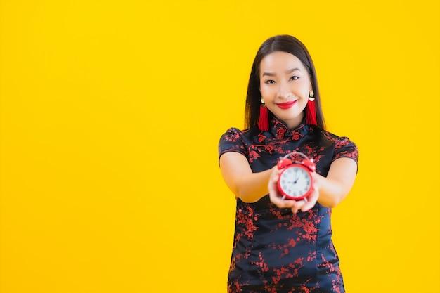美しい若いアジアの女性の肖像画はチャイナドレスを着て時計を示しています 無料写真