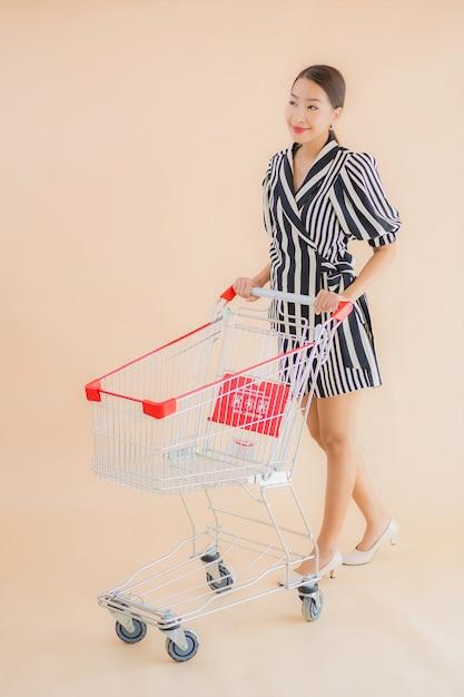 ショッピングカートと美しい若いアジア女性の肖像画 無料写真