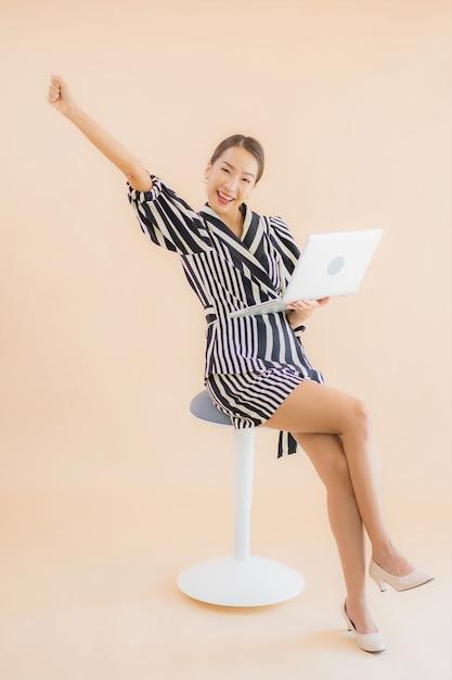 ラップトップまたはコンピューターと美しい若いアジア女性の肖像画 無料写真