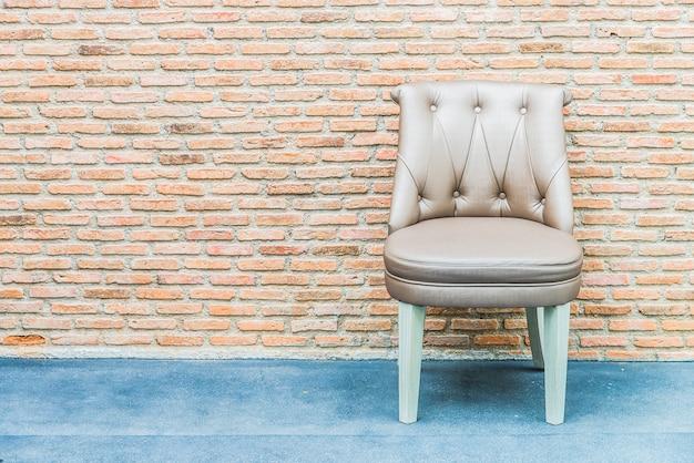 レンガの壁の背景に高級革製の椅子 無料写真
