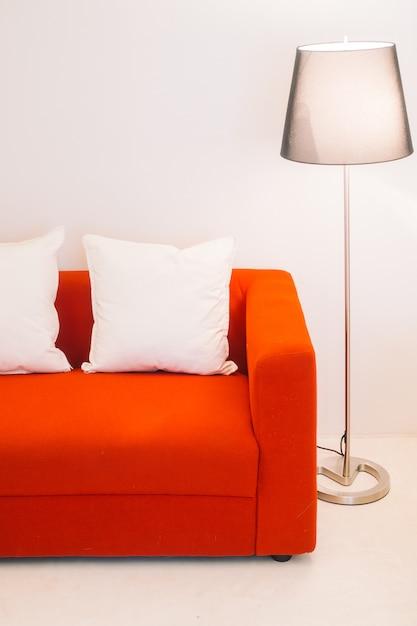 Красный диван с подушкой и лампой Бесплатные Фотографии