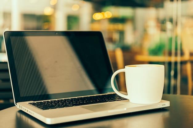 ノートパソコンのコーヒーカップ 無料写真