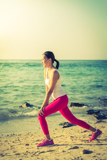 Действие йоги молодой женщины на пляже Бесплатные Фотографии
