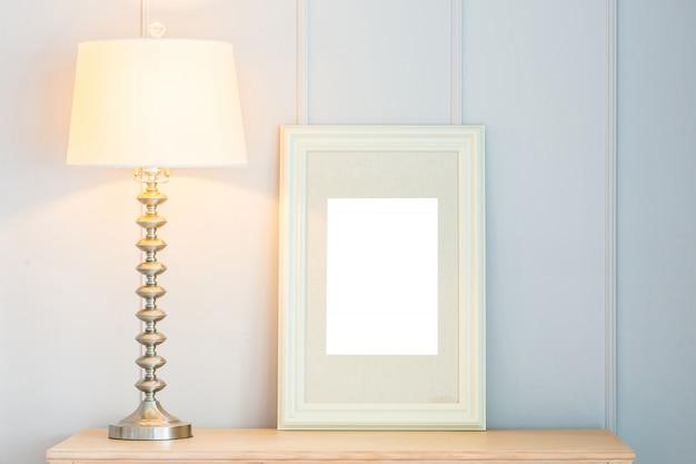 テーブル上のライトランプの装飾と空のフレーム 無料写真