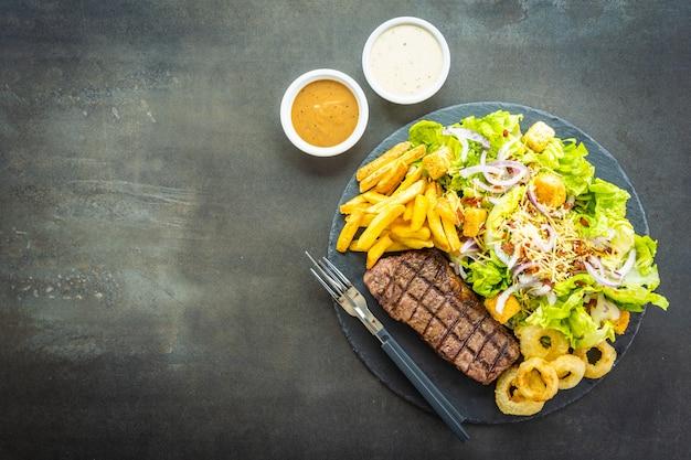 フライドポテトオニオンリングと牛肉のグリルステーキ 無料写真